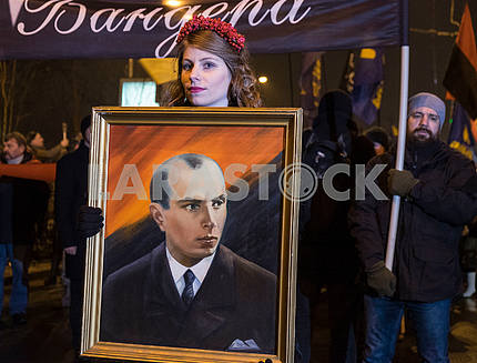 A girl holding a portrait of Bandera