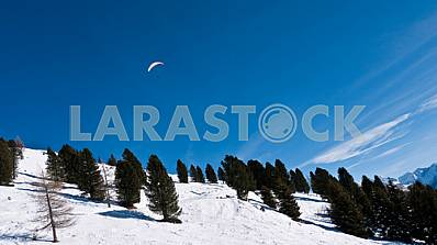 Paratrooper in the sky over the mountain slope
