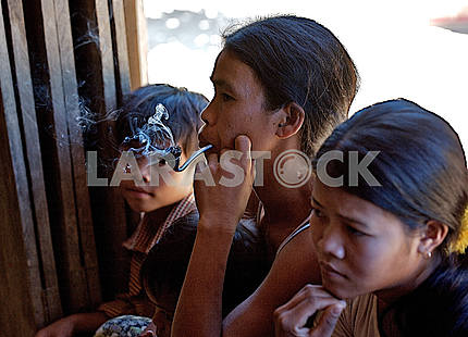 Mother and children with a pipe.Cambodia. In the jungle, the fa