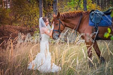 Brown-haired woman standing in front of a horse, in wedding dress mermaid silhouette, among the spikelet, autumn, forest on the background