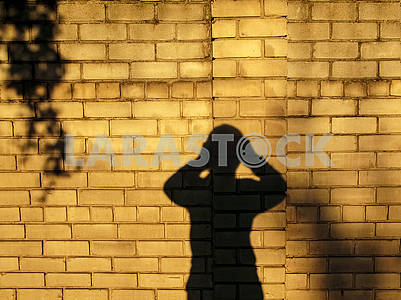 Shadow of a man, who holding on behind his head.