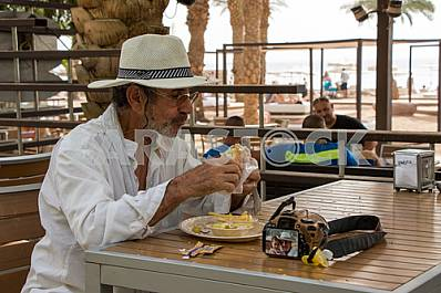 The man in the hat is eating at a cafe in Eilat