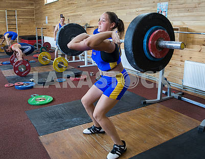The girl lifts the barbell