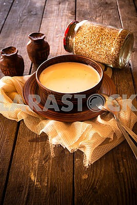 Boiled buckwheat with milk in wooden bowl on rustic wooden background, vertical image