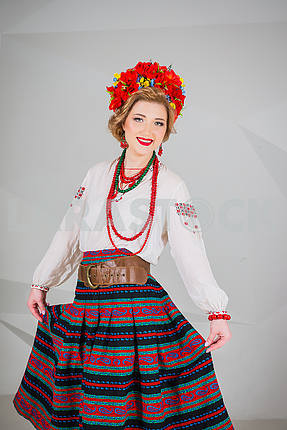 a beautiful girl in National Ukrainian Costume. captured in studio. Embroidery and jacket. wreath. circlet of flowers. red lips