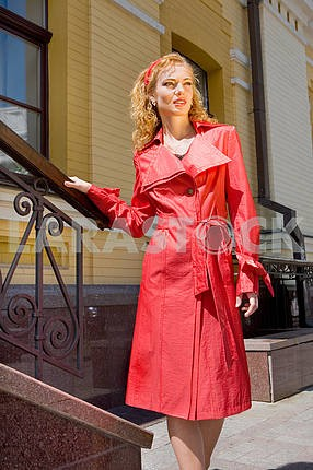 Beautiful Young Woman in red clothes. Near the stairs