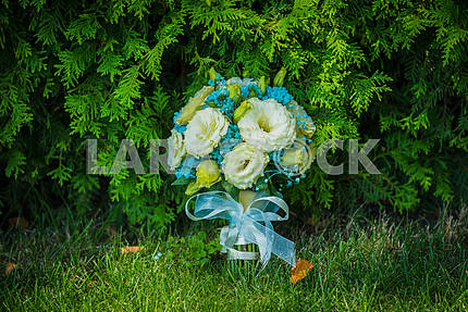 Wedding bouquet standing near the thuja tree, with blue ribbon, green grass and some autumn leaves near