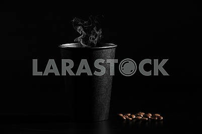 A black glass of hot coffee with scattered coffee beans on a black background. close-up