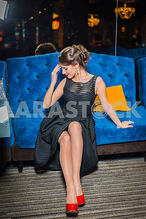 Beautiful brunette woman sitting in the restaurant, in black dress and red shoes. Smiling with her red lips, shy like a little girl