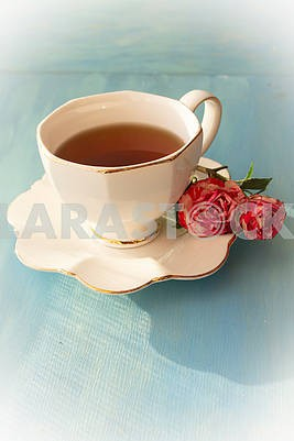 White cup of tea and roses on blue background