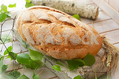 Traditional whole wheat bread on rustic wooden table with birch branche