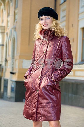Beautiful Young Woman in brown coat and cap. Smiling young woman