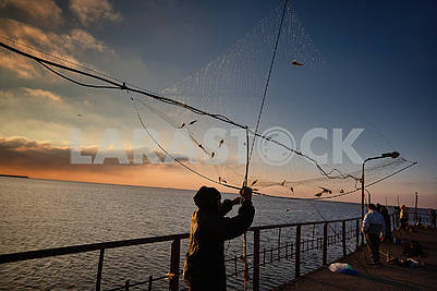 Fisherman by the sea at dawn
