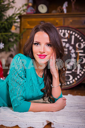 Portrait beautiful brunette woman lying on the floor among the new years decorations in bright blue dress, smiling