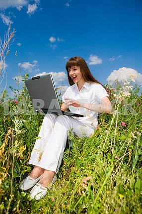 Happy Young Woman on the grass field with a laptop