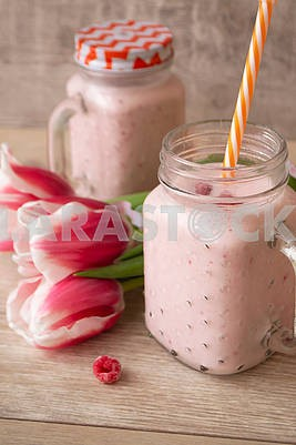 Pink raspberry cream smoothie in mason jar and tulips