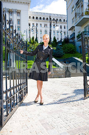Beautiful Young Woman in black coat end boots. Against the backd