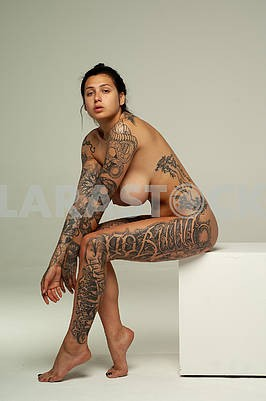 Young beautiful girl with tattoo posing nude in studio sitting on a white cube