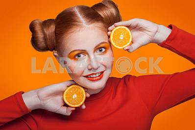 Young beautiful fashion model with orange. studio shot.