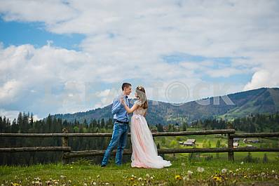 Couple in love looking at each other, dancing, Carpatian mountains on the background,  clouds, old wooden fence, girl in long tulle dress, romantic landscape, wedding walk on nature