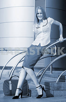 Young woman, blond, against the backdrop of the station. In all