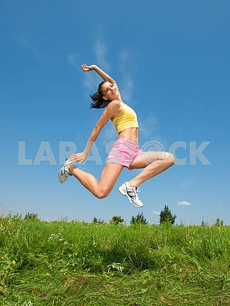 young athletic girl jumping on grass