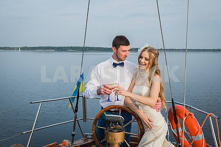 Helm of yacht. The steering wheel of the yacht. Yachting. Guy teaches the girl of yachting. Guy and girl hands on the wheel. Love story. Lovers on a yacht. Wedding on  sailing yacht.