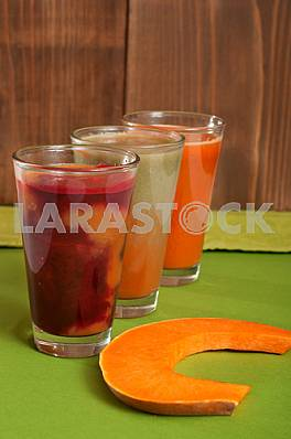 Various freshly squeezed vegetable juices with the hunk of pumpkin on green background.