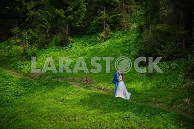 Wedding in mountains, a couple in love, in mountain forrest, standing on the path, among the lawn with the green grass, rustic style, kissing each other, girl in long tulle dress, romantic landscape