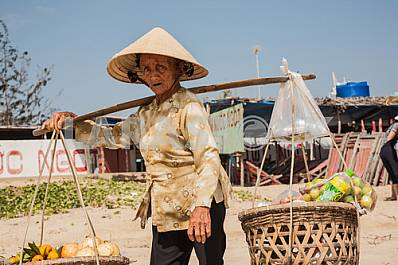 Grandmother, a saleswoman of fruits and vegetables on the beach