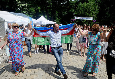 A man with the flag of Azerbaijan on his shoulders dancing