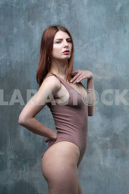 Young beautiful girl pose in a brown bodysuit in the studio
