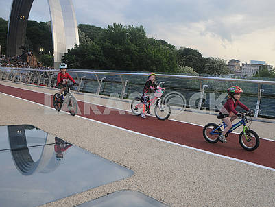Children riding bicycles over the bridge