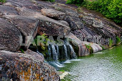 Unique waterfalls, water flows out of large boulders.   Tract cascades.