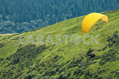 Paraglider flying over mountains on a summer day