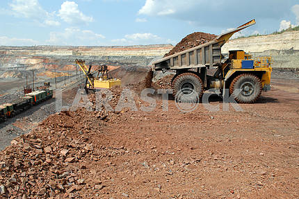 Dump-body truck unloading in mine