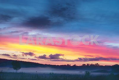 Beautiful colorful sunset in a hilly valley
