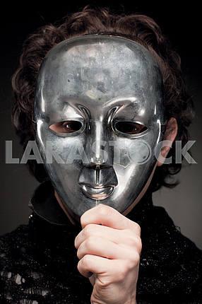 Мужчина проведение его руку перед маски