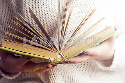 Young girl reading an open old book. Knowledge, Science. Toned image.