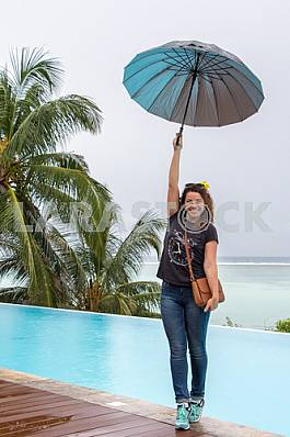Girl standing with umbrella in hand on background of ocean