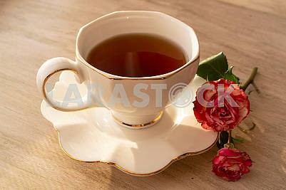 Healthy tea in white classic cup with roses, vintage image