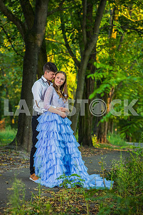 A love story couple, in love, together in the forrest park,  girl in a beautiful violet dress, sunny evening, summer, holding each other