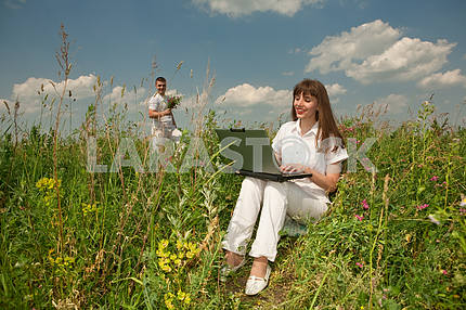 Happy Young Woman on the grass field with a laptop against the b