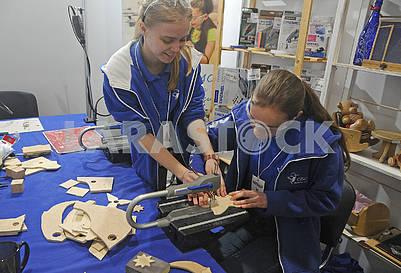 Девушки вырезают  фигурку из куска фанеры