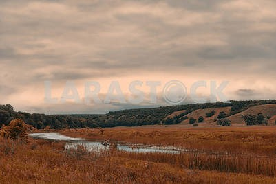 Fisherman in a boat on a small lake in a cloudy hilly valley