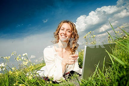 Young woman lie grass with a laptop. Against blue sky.