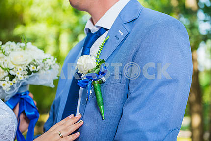 Boutonniere for the groom, on the blue jacket, close up