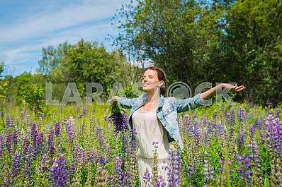 Young woman, brunette, happy, standing among the field of violet lupines, smiling, purple flowers. Blue sky on the background. Summer, sunny day!
