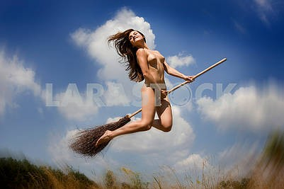 Young naked girl jumping with a broom