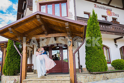 A wedding couple, groom holdin the bride on hands in the front of an entrance to an old hotel. sunny day, lovely couple. groom carrying bride